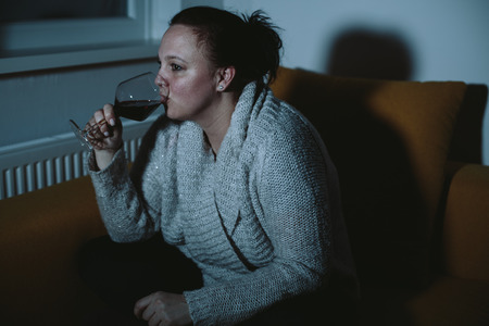 plus sized: Overweight woman watching TV drinking wine