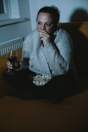 plus sized: Overweight woman watching TV eating popcorn drinking wine Stock Photo
