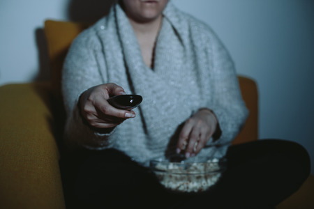 plus sized: Close up of overweight woman watching TV with glass of wine and popcorn