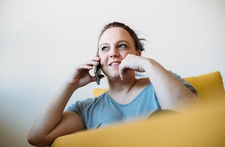 Surpoids femme parlant au téléphone sur le canapé Banque d'images - 44417270