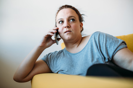 plus sized: Overweight woman talking on phone on the couch Stock Photo