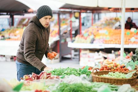 若い男ファーマーズマーケットで新鮮な野菜を購入