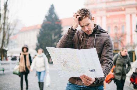 confundido: Turista perdido mirando el mapa de la ciudad en un viaje. Busca direcciones. Foto de archivo
