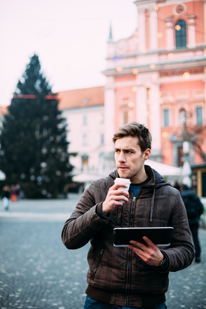one man: Young man drinking coffee on street while  tablet computer Stock Photo