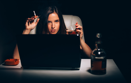 creative writer: Sexy young woman smoking and drinking whiskey at her desk