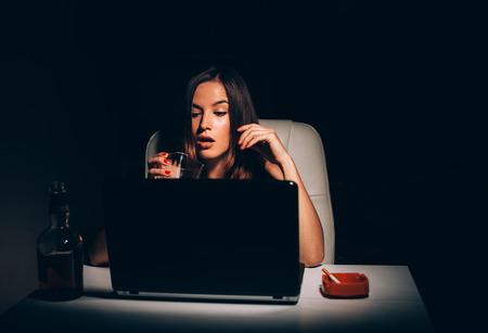novelist: Female novelist smoking and drinking while writing novel book