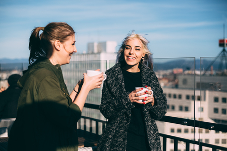 roof top: Hip young women talking in roof top cafe