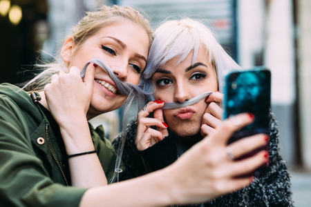 women hips: Silly Young women best friends taking a selfie Stock Photo