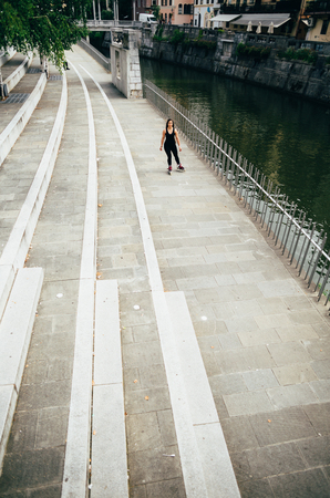 blading: Young curvy woman rollerskating on riverbank