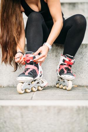 rollerskating: Young woman tying rollerskates