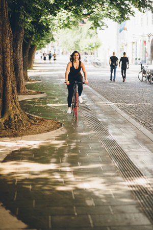 curvy: Curvy young woman riding fixie bicycle in a city