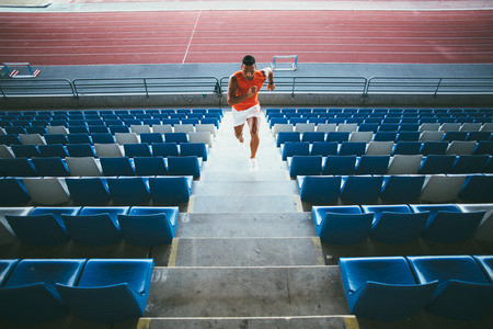 tribune: Young man working out on stadium tribune steps