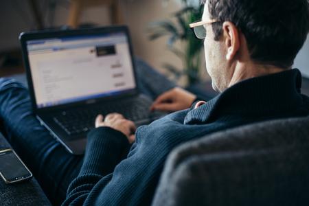 trabajando en casa: el empresario de mediana edad que trabajan desde su casa cómoda en el sillón