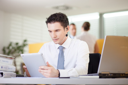 Businessman talking on phone and using tablet computer in office photo
