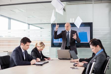 enfado: Jefe perdió los estribos durante la reunión. Empleados asustados están mirando hacia abajo.
