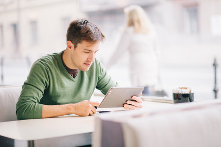 Young man using tablet computer in cafe Stock Photo