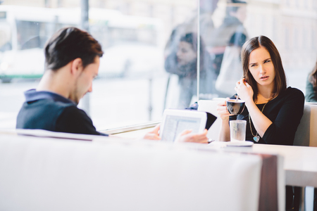 up to date: Millennial couple fighting arguing in coffee shop