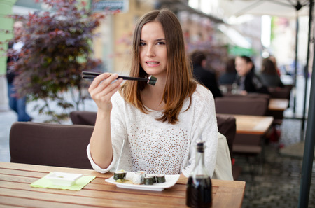 Hesitatnt young woman eating sushi first time