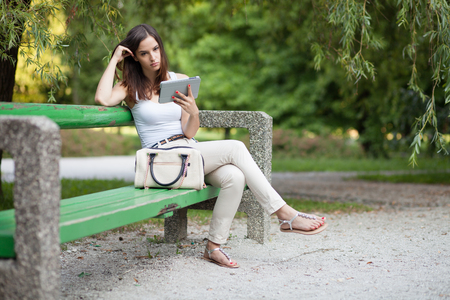 persona pensando: Pensativo mujer joven con tablet PC en el parque