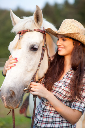 Young woman cowgirl holding caressing white horse photo