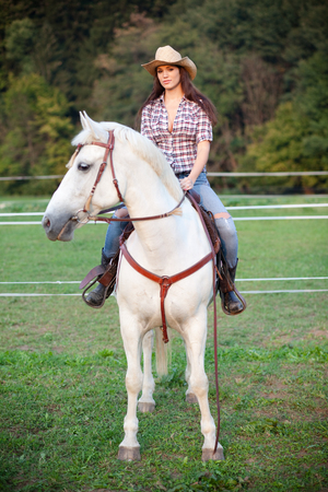 Young woman cowgirl riding white horse photo