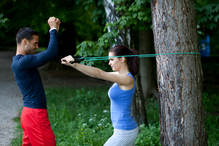 execute: Personal trainer showing his client how to properly execute biceps exercise with resistance band