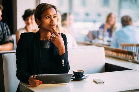 Nadenkend zwarte zakenvrouw met behulp van tablet pc in de coffeeshop Stockfoto