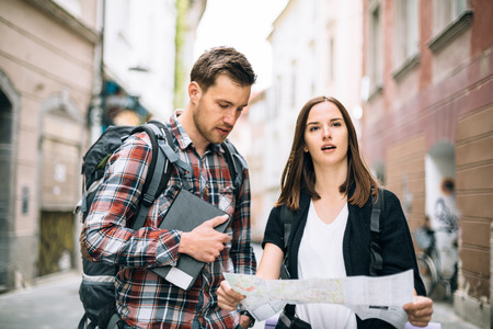 Millennial couple backpackers traveling looking at map