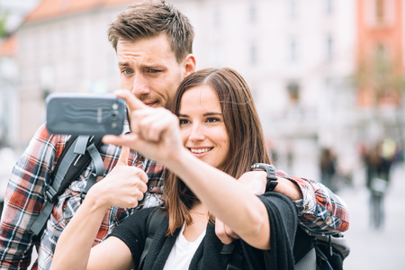 Millennial couple backpackers traveling taking selfie photo