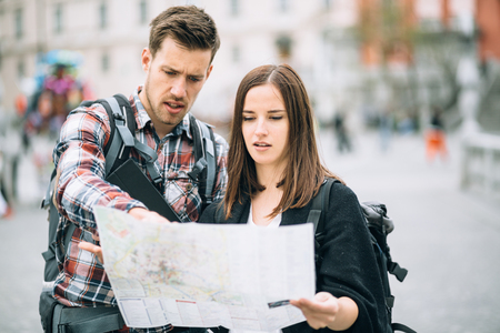 Millennial couple backpackers traveling looking at map photo