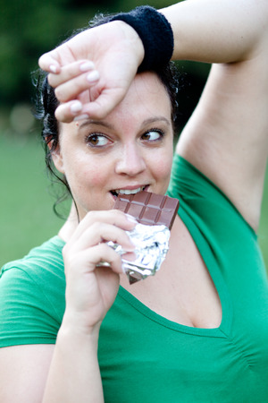 Fat overwight plus sized young woman eating chocolate after training workout