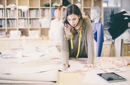 Fashion designer working on designs drawing in studio