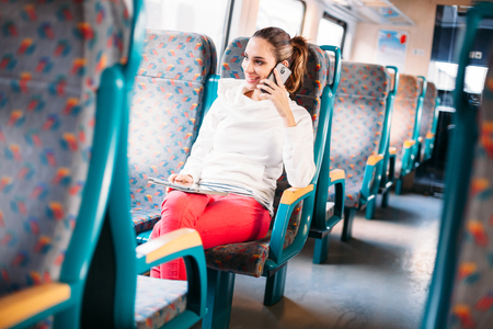 Millennial young woman talking phone train traveling photo