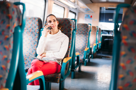 Millennial young woman talking phone train bus traveling photo