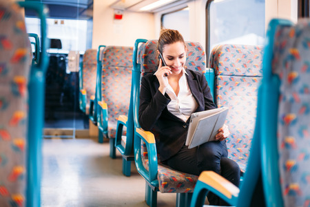Young millennial businesswoman traveling train bus talking phone photo