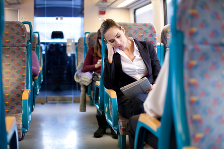 Millenial businesswoman using tablet computer bus train photo