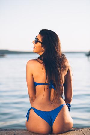 Jeune femme subjuguée allongée sur la plage Banque d'images - 79062026