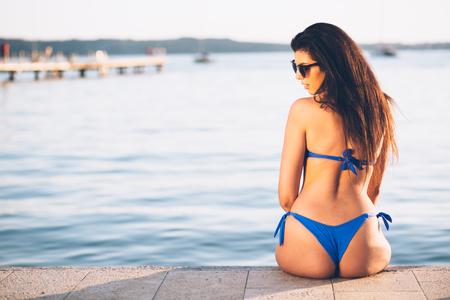 ビーチ海の上の桟橋に座っていた若い女性 写真素材