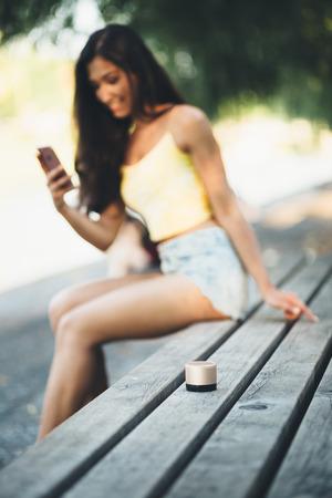 젊은 천년 여자 공원 벤치에서 음악을 듣고 스톡 콘텐츠