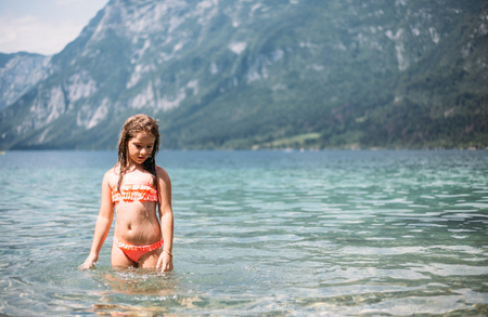 Little girl in lake surrounded by mountains Archivio Fotografico