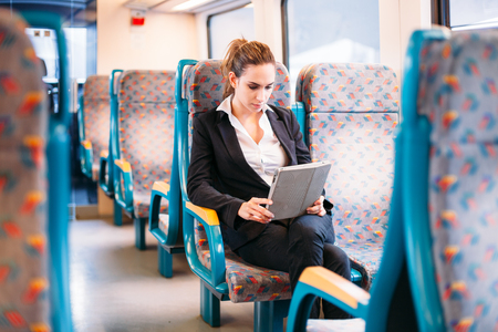 Young millennial businesswoman traveling train bus tablet computer