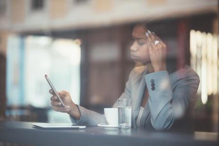 커피 숍에서 심각한 젊은 흑인 사업가 문자 메시지 스톡 콘텐츠