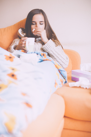 Sick young woman blowing her nose on sofa