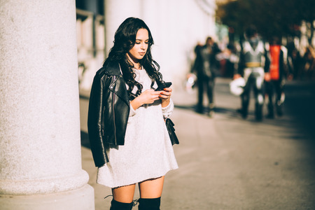 Young millennial woman using phone on street texting calling Stock Photo