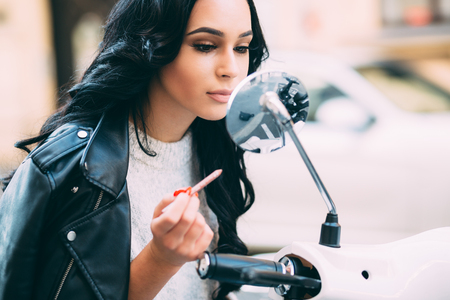 Young millennial woman applying make up on street