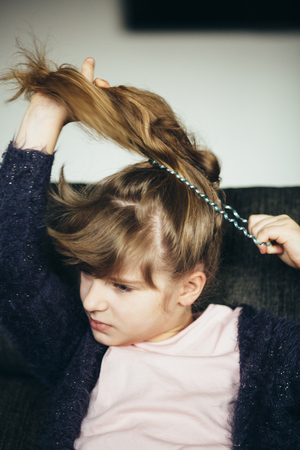 Little girl making a ponytail at home Stock Photo