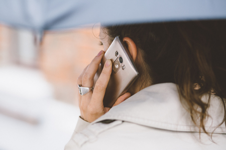 Woman talking on the phone in the rain Stock Photo