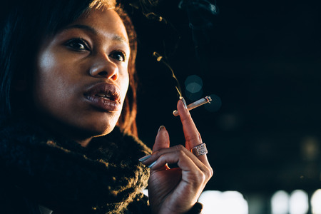 Young woman smoking marijuana in abandoned industrial building Stock Photo