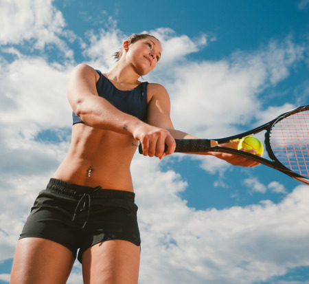 Young woman tennis player serving hitting the ball