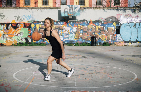 Female basketball player dribbling the ball on outdoor court 스톡 콘텐츠